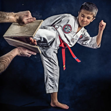 Taekwondo boy breaking a board.
