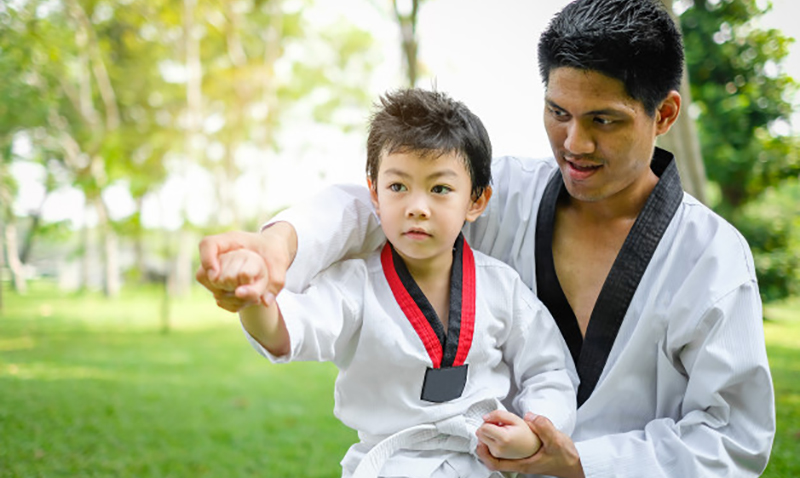 father-is-teacher-teaching-taekwondo-kids-children-boy-are-learning-nature_33855-172